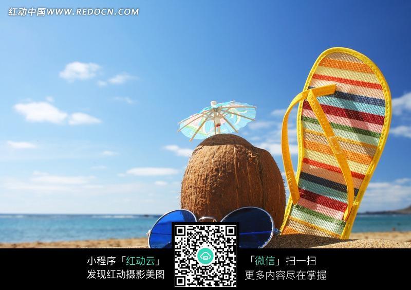 沙滩上的太阳镜拖鞋和椰子图片