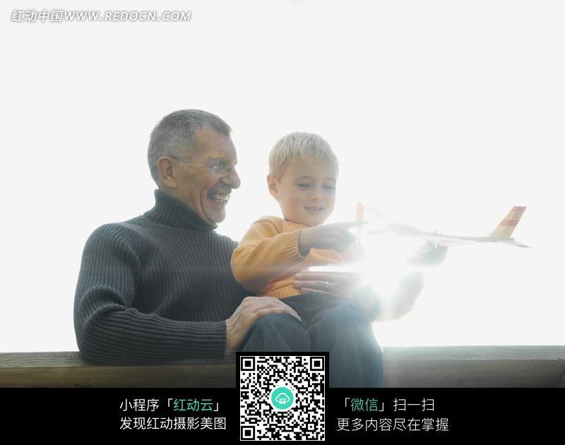 微笑陪着孙子玩飞机模型的外国老人图片