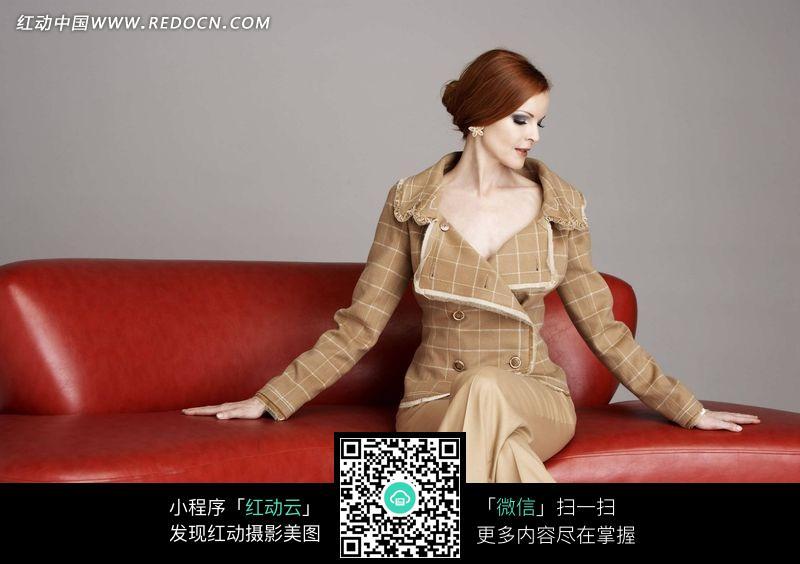坐在红沙发上低着头的外国美女图片