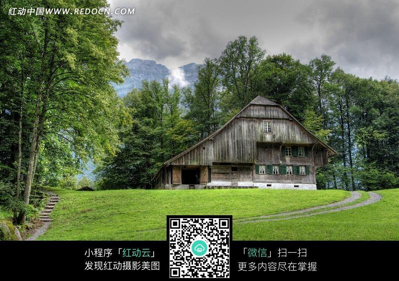 树林围绕的小木屋和草地图片图片