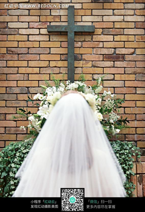 十字架下穿婚纱的新娘背影头部图片
