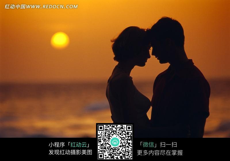 在海边黄昏下相拥的情侣