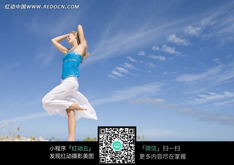 山坡上单腿站立的女人图片
