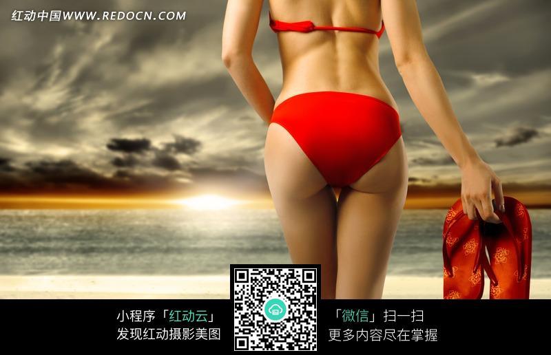 沙滩上穿红色比基尼手提红色拖鞋的美女背影图片