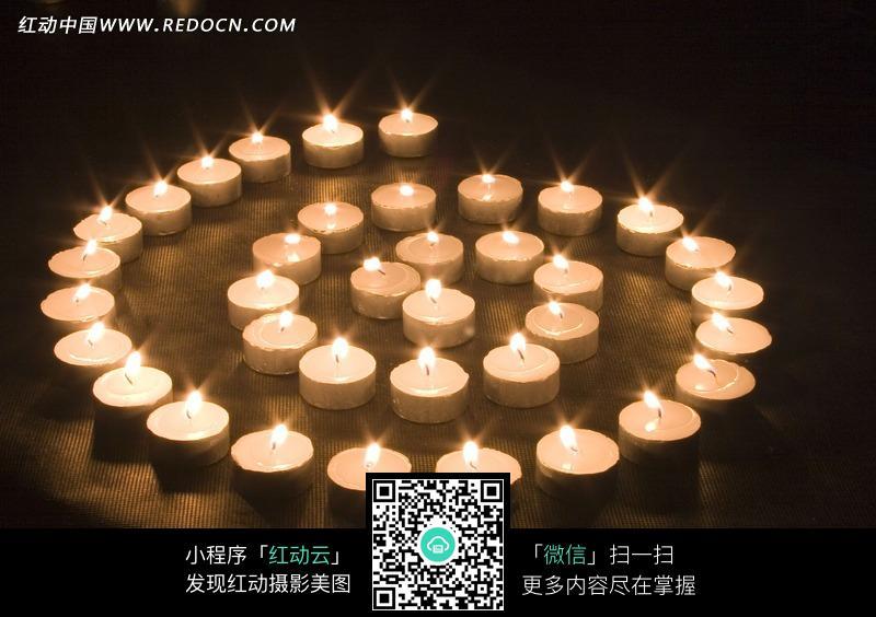 摆成螺旋状点燃的白色蜡烛