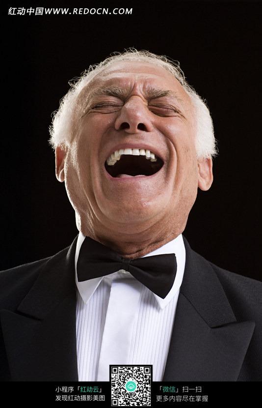 扎黑色领结仰头大笑的外国白发男人图片