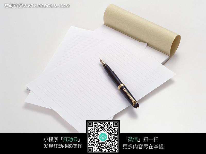 散落的信纸和纸上的钢笔图片