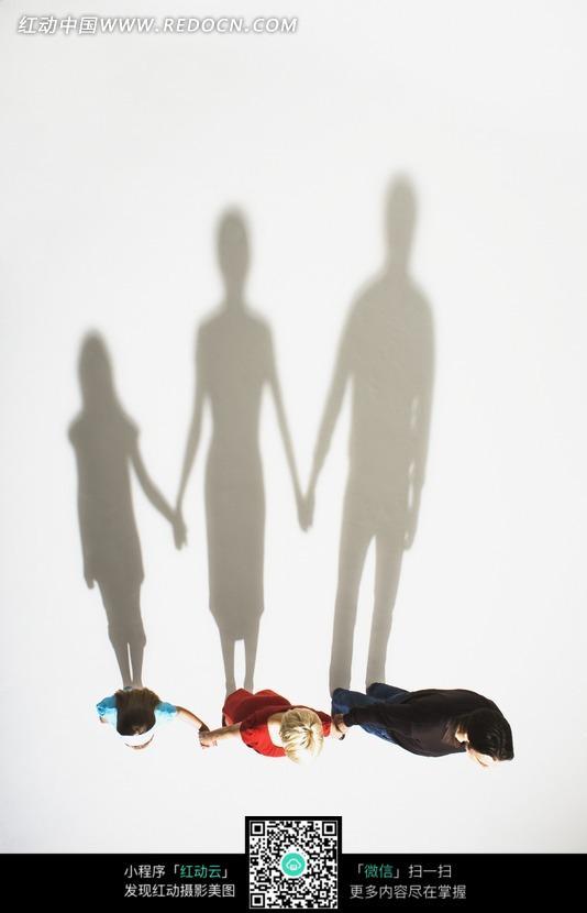 手拉手的一家人与他们的影子