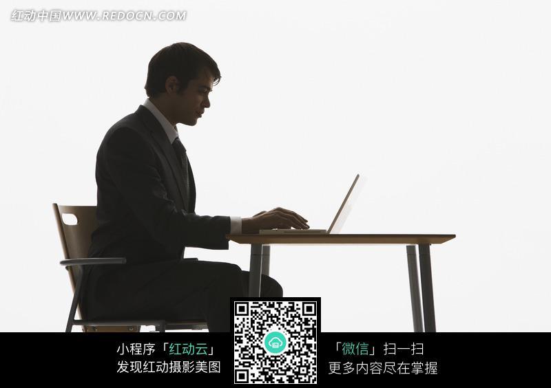 在桌上录入电脑的男人侧脸图片