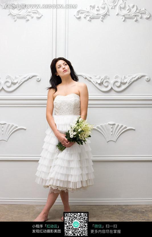 手拿鲜花仰望的白衣美女