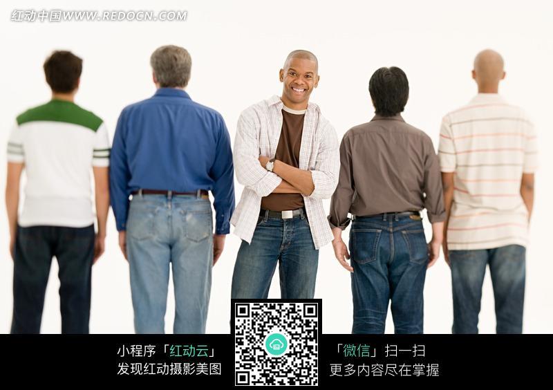 四个背面站立的男人中的一个正面站立的男人