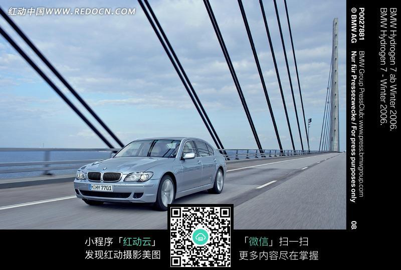 大桥上行驶的银色宝马汽车图片