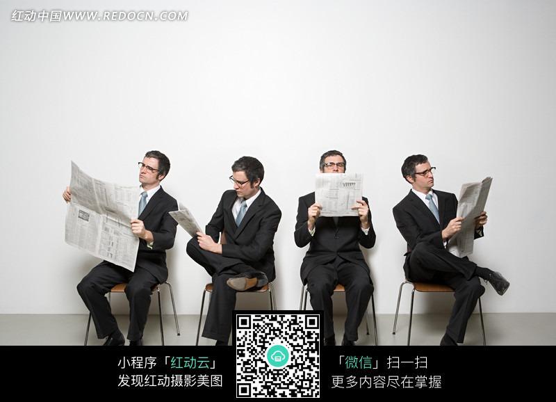 四个坐在凳子上看报纸的男人图片