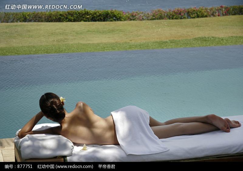 侧躺在床上的半裸美女和远处海水旁的草地图片