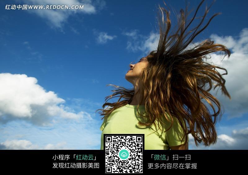 蓝天白云下甩头发的绿衣美女图片