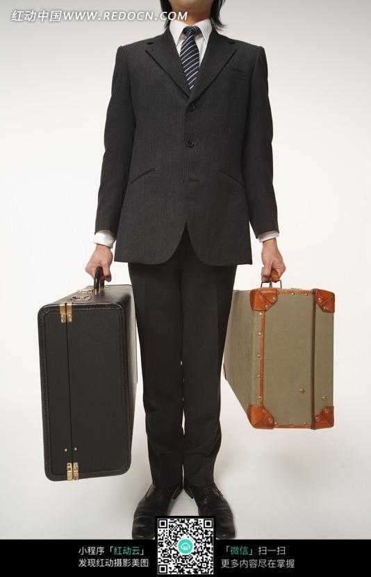 穿深褐色西装双手提着行李箱的男人图片