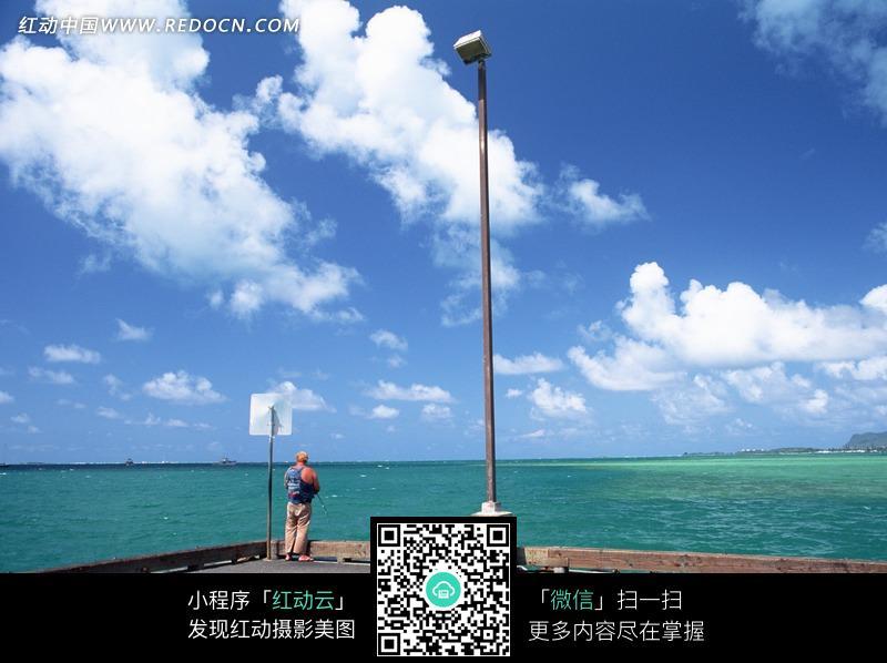 蓝色大海码头的灯柱和男人背影图片