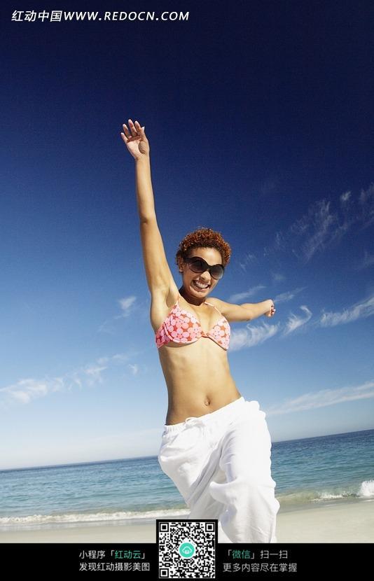 海边沙滩穿着白色裙子跳跃的外国美女图片 竖
