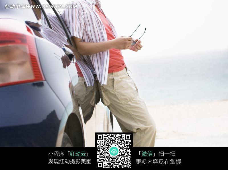 海滩沙地背靠汽车拿着眼镜的男士身影