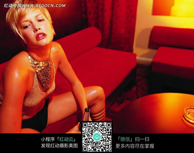 坐在红色沙发上双手拿着酒瓶的美女图片