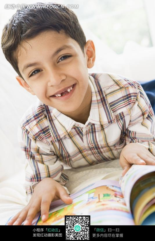 扑在床上看书的印度小男孩