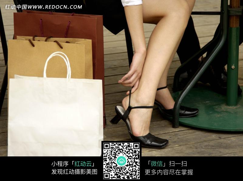 手机 购物袋/购物袋和坐着提鞋的女人脚部特写