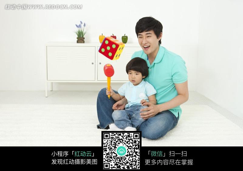 手拿玩具坐在爸爸腿上的小女孩图片