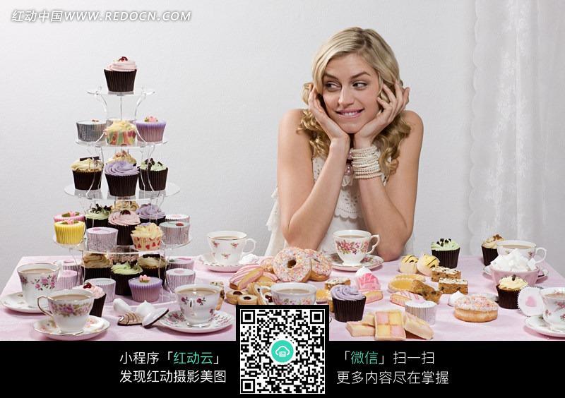 看着餐桌上甜品蛋糕的美女图片