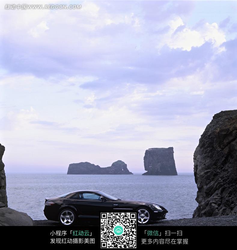 停放海边石头旁边的黑色汽车图片