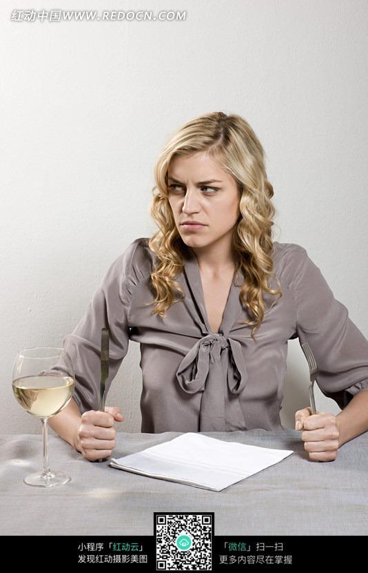 餐桌前手拿餐具的外国女士愤怒表情照片图片