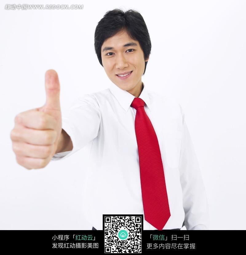 起右手大拇指穿白衬衣红领带的男士