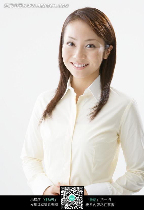 穿着白衬衣看着前方微笑的美女图片
