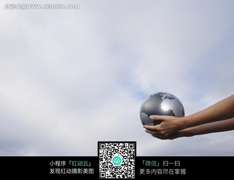 双手托着一个灰色地球仪