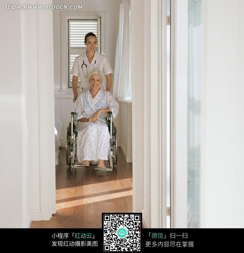 外国护士推着坐在轮椅上的老人