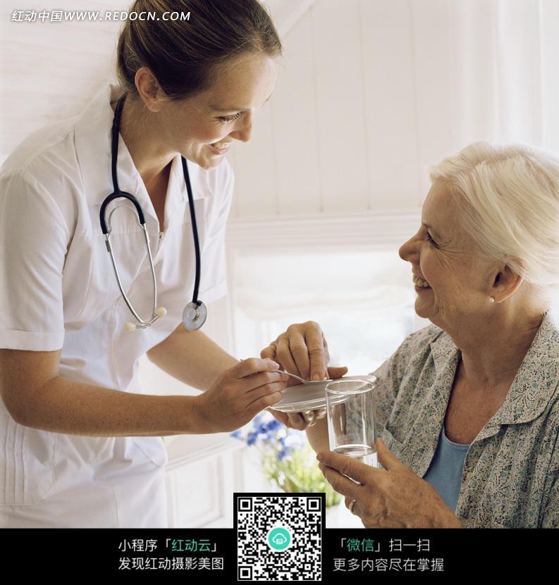 给老人拿药的外国美女护士图片