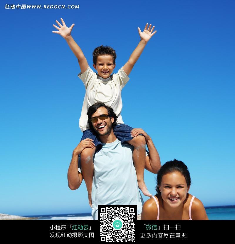把孩子架在肩上陪孩子在海边玩耍的外国父亲