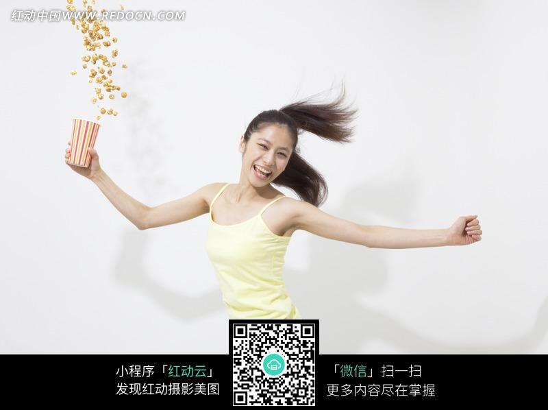 黄色衣服拿爆米花的女人图片