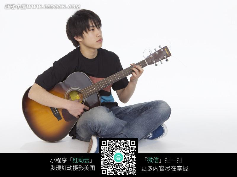 盘腿坐着弹吉他的男孩