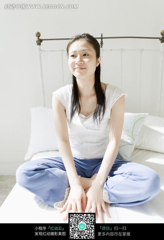 盘腿坐在床上的女孩图片