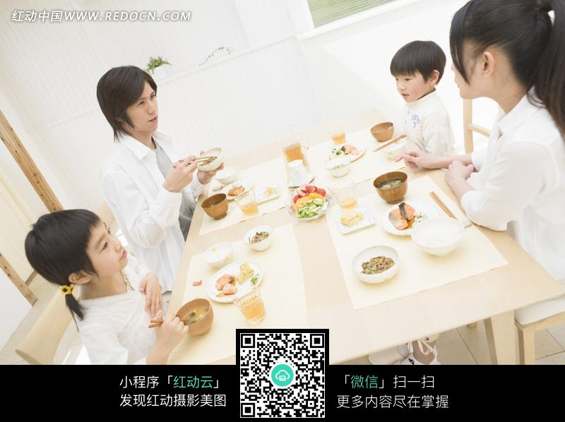 坐在餐桌前吃饭的一家人图片