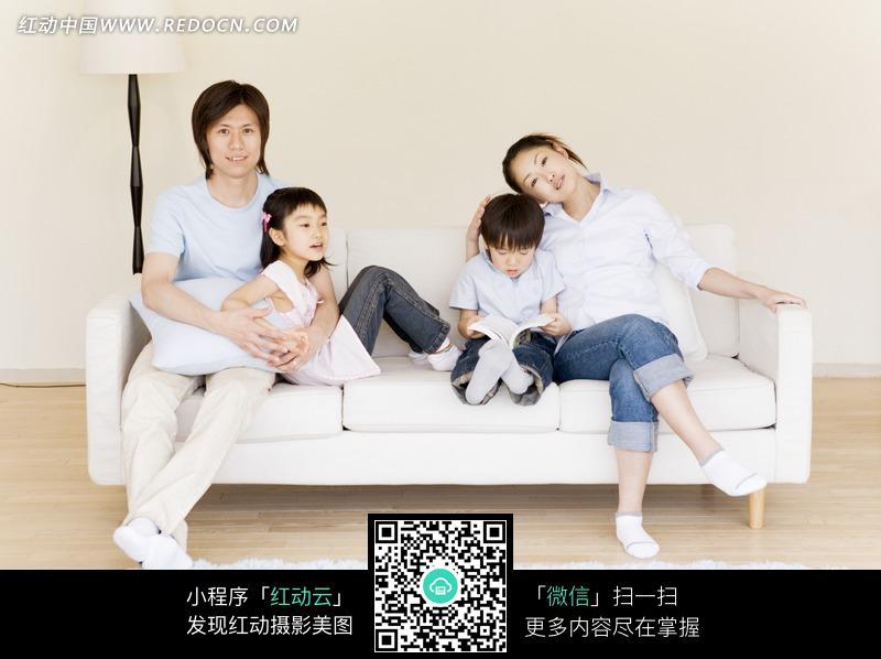 沙发上年轻夫妻抱着小男孩小女孩图片