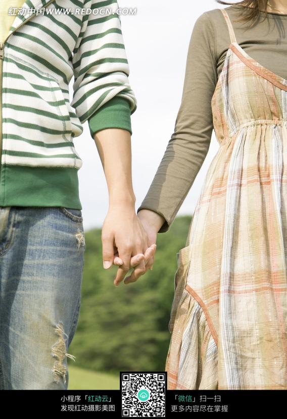 手牵手的两个人在草地上图片