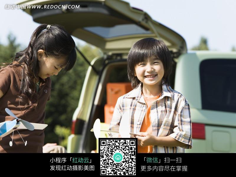 汽车旁边玩耍的小男孩和小女孩图片_日常生活