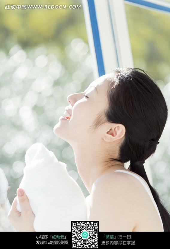 窗户下拿着毛巾抬着头的美女侧脸图片 日常生