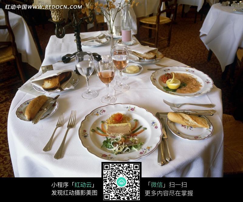 餐桌上盘子里的食物和香滨酒