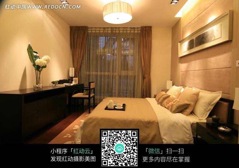 白色吊灯下的装饰画和褐色的床图片