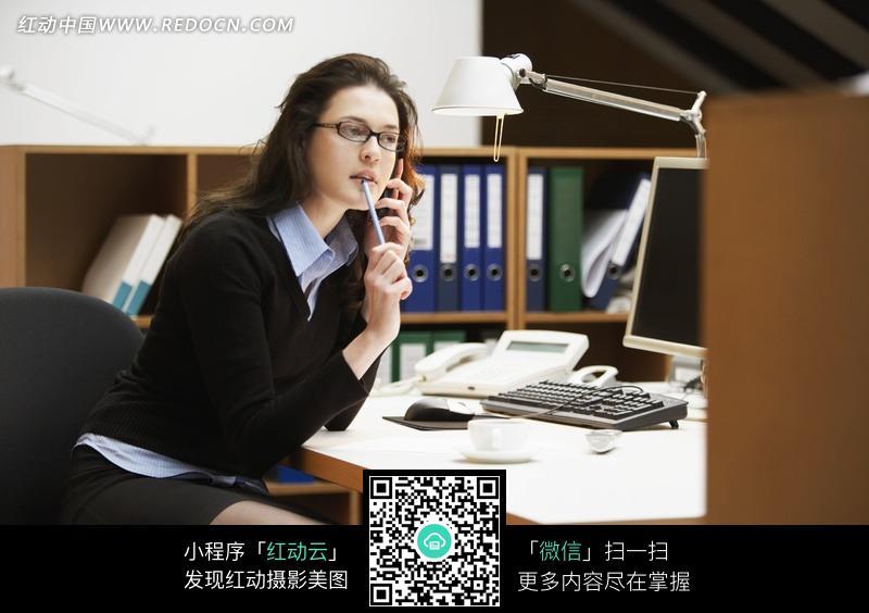 办公桌边嘴含笔打电话的职业装美女图片(编号2鬼传讨美女图片