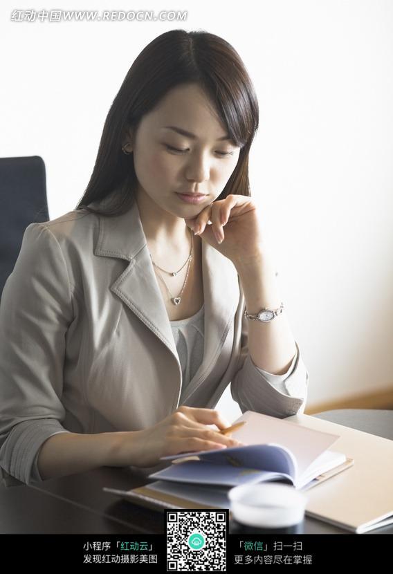 美女 职业装-坐在办公桌前看笔记的职业装美女