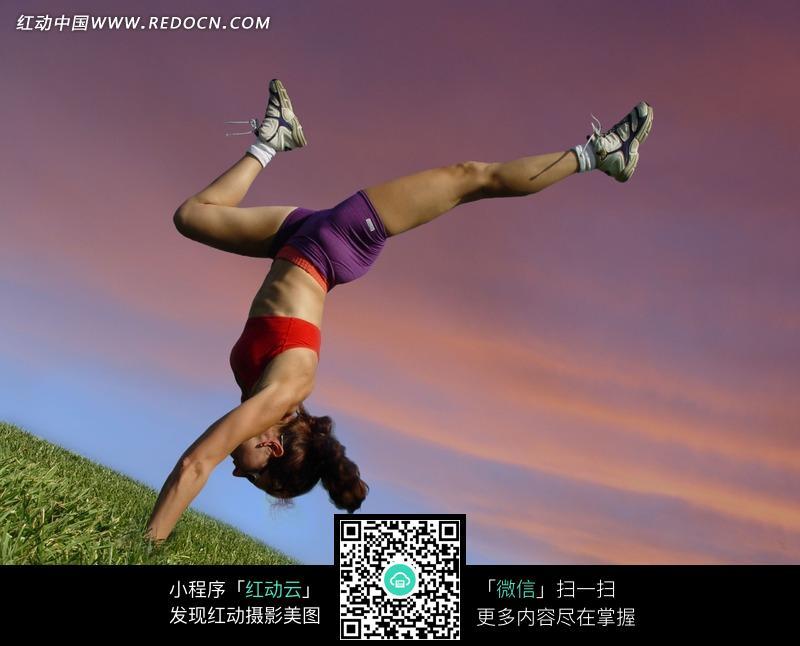 草地上倒立的运动装女人图片