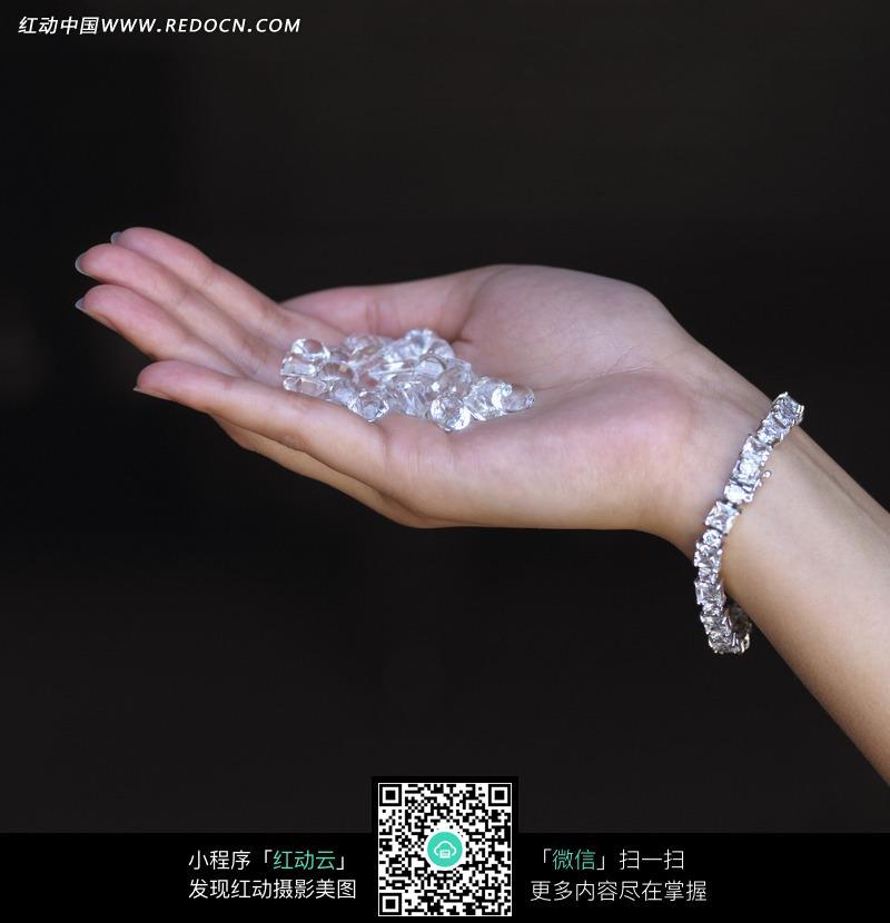 捧着钻石颗粒戴钻石手链的女人的手图片